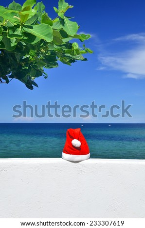 Santa hat on the white wall overlooking tropical sea -- Tropical christmas vacation concept