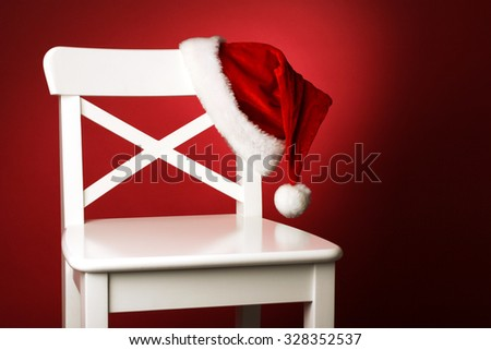 Santa hat on white chair front of red background #328352537