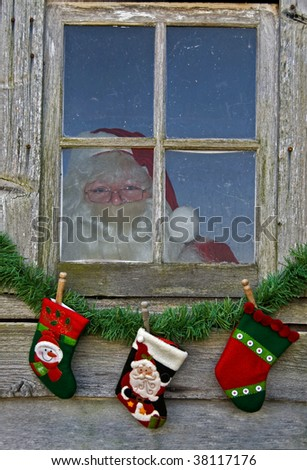 Santa in old window with stockings - stock photo