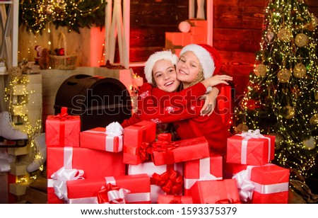 santa kids with present box. Find presents online. Christmas together. What a great surprise. happy little girls. xmas celebration mood. sisters love family holiday. Wishing a happy New Year.