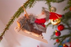 Santa Klaus on a his snow sledge (sled). Beautiful original Christmas ornament hanging on a tree branch. December winter holidays.