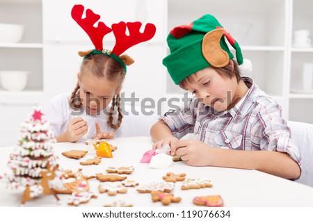 Santa little helpers - reindeer and elf - decorating gingerbread cookies at christmas time
