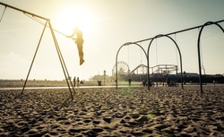 santa monica beach. silhouette of a woman going up with the swing. concept about traveling,united states and people