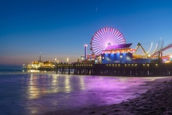 Santa Monica Pier illuminated with new LED lights at night with a reflection that can be seen on the waves.