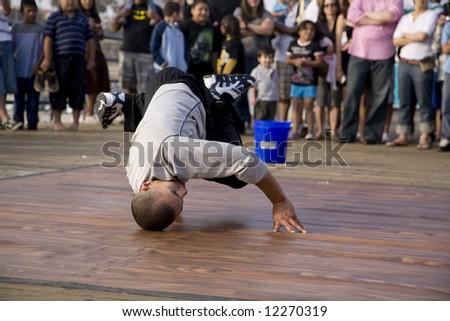 Santa Monica Pier, Santa Monica, CA May 3rd, 2008:  B-Boy street performer breakdancing for the crowd performing a headstand lock