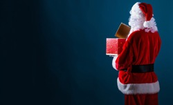 Santa opening a gift box on a dark blue background