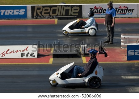 SANTA POD, UK - APRIL 23: Alternative energy racing at Santa Pod Raceway. Two Sinclair C5 electric vehicles on the quarter mile drag strip. April 23, 2010, Santa Pod, UK. - stock photo