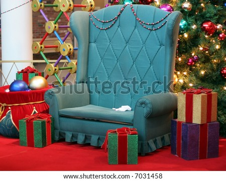 Santa's chair surrounded by presents and christmas tree