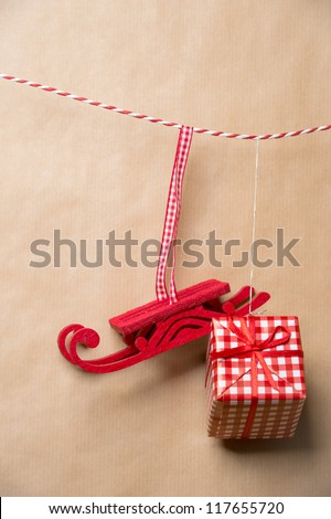 Santa's fairy Christmas decorative sleigh and gift box hanging on a ribbon. Old brown paper background