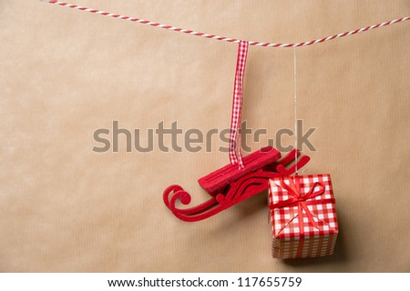 Santa's fairy Christmas decorative sleigh and gift box hanging on a ribbon. Old brown paper background. Lots of copyspace