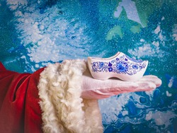 Santa's hand with typical Dutch traditional souvenir clogs on a blue background.