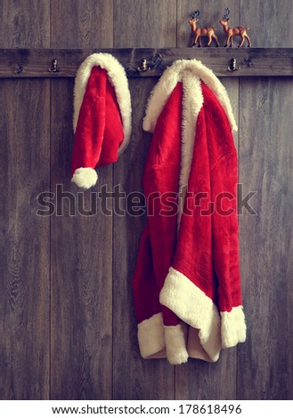 Santa\'s hat and coat hanging from the coat rack - vintage tone effect