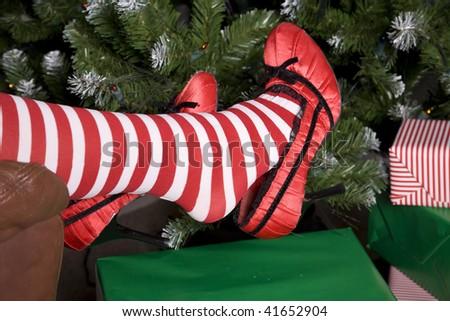 Santa's helper putting her feet up by the Christmas tree taking a break.