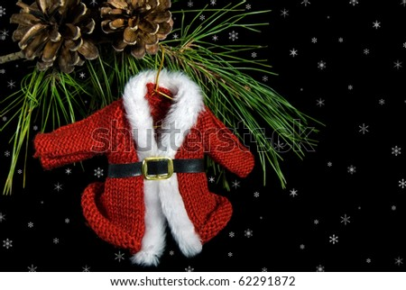 santa's sweater coat hanging from a pine bough