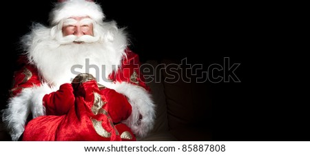 Santa sitting at the Christmas room and looking into the sack