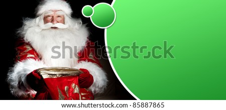 Santa sitting at the Christmas room and looking into the sack. Blank graphic balloon with lots of copyspace for your text and logo overhead