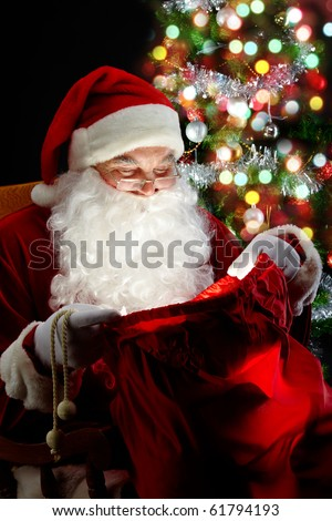 Santa sitting at the Christmas tree and looking into the sack