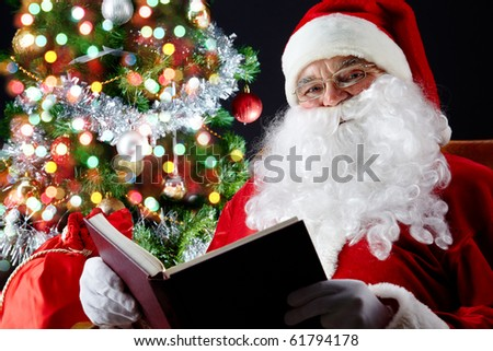 Santa sitting at the Christmas tree and reading a book
