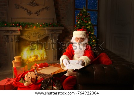 Santa sitting at the Christmas tree, holding Christmas letters and having a rest by the fireplace.