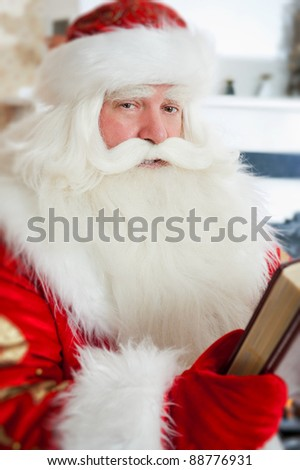 Santa sitting at the Christmas tree, near fireplace and reading a book. Indoors