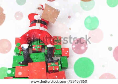 Santa sitting at the top of many big gift boxes and reading wish list. Black Friday 2017 at United States. Wishes. Copy space at white background. Cristmas shopping. Xmas, New Year Merry Christmas #733407850