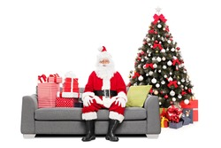 Santa sitting on a sofa by a Christmas tree isolated on white background