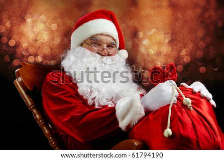 Santa sitting with a sack against glaring lights