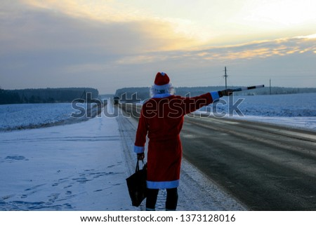 Santa stops the car with a police baton. On the winter road at sunset