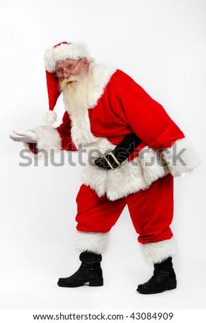 santa tiptoeing walking secretly studio shot on plain background - stock photo