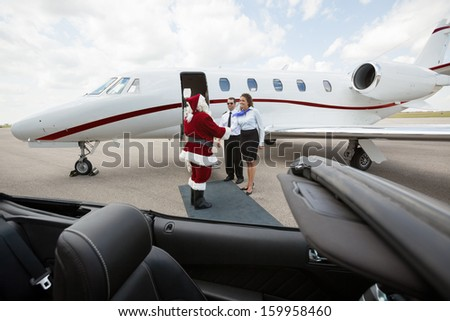Santa travelling on a private jet meeting cabin crew
