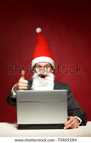 Santa with laptop showing thumbs up