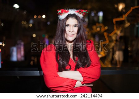 Santa woman dressing. Smiling and active. Is decorated with lights that happy during Christmas. #242114494