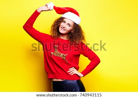 Santa woman in christmas hat wearing red sweater with deer smiling having fun laughing rejoices touches touches on yellow background in the studio. The concept of the holiday of Christmas and New Year #740943115