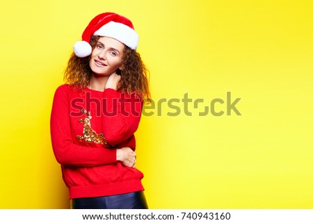 Santa woman in christmas hat wearing red sweater with deer smiling having fun laughing rejoices touches touches on yellow background in the studio. The concept of the holiday of Christmas and New Year #740943160