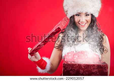 Santa woman in hat opening box with present,red background
