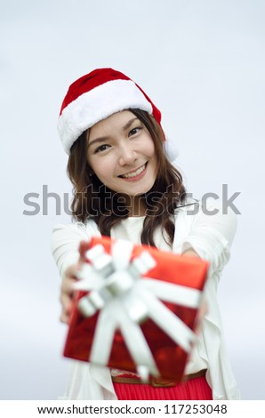 Santa woman showing gift wearing Santa hat. Christmas woman portrait of a cute, beautiful smiling Asian model. Isolated on white background