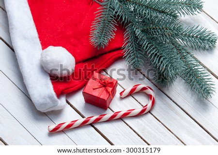 Santas hat and christmas candy with brench and red gift on white wooden table.