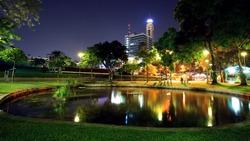 Santipap Park with skyline reflection on the pond at dusk in Bangkok, Thailand