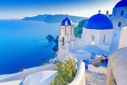 Santorini, Greece. Charming view Oia village on Santorini island. Traditional  famous blue dome church over the Caldera in Aegean sea. Traditional blue and white Cyclades architecture.