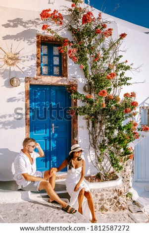 Santorini Greece, young couple on luxury vacation at the Island of Santorini watching sunrise by the blue dome church and whitewashed village of Oia Santorini Greece during sunrise during summer