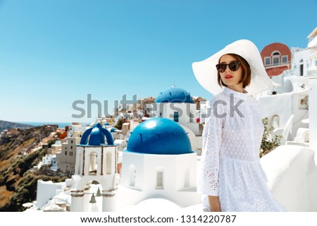 Santorini. Holidays. Young woman in summer dress, glasses and hat is enjoying the sunny weather outside #1314220787