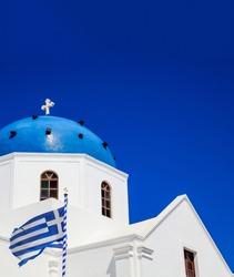 Santorini island, Greece. Greek flag waving on white orthodox church with blue dome against blue clear sky background, vertical photo