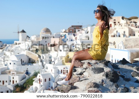 Santorini Oia Greece  Young woman looking out over the village Oia #790022818