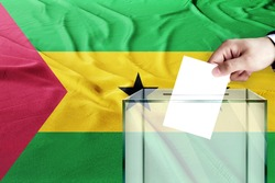sao tome and principe flag, sao tome and principe  the symbol of elections Male hand puts down a white sheet of paper with a mark as a symbol of a ballot paper against the background of the