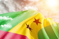Sao Tome and Principe national flag cloth fabric waving on beautiful grey sky.