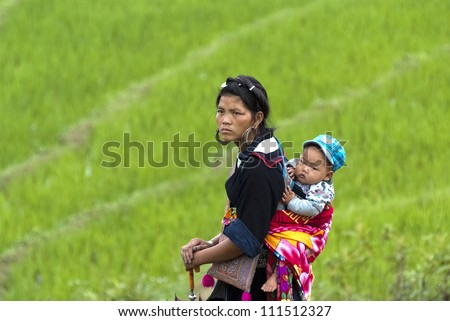 SAPA, VIETNAM- JULY 6: Hmong woman carries her child on the back on July 6 2009 in Sapa, Vietnam.  Black Hmong women are known for their indigo-dyed costumes and wrap long scarves around their legs.