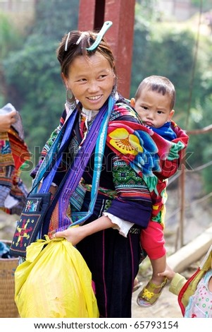 SAPA,VIETNAM - NOV 23: Unidentified girl of the H'mong Ethnic Minority carries baby on November 23, 2010 in Sapa, Vietnam. H'mong ethnic minority in Vietnam have a population just under 600,000.