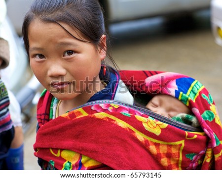 SAPA, VIETNAM - NOV 22: Unidentified young girl of the Black H'Mong Ethnic Minority People carries baby on November 22, 2010 in Sapa, Vietnam.  H'Mong are the 9th largest ethnic group in Vietnam.