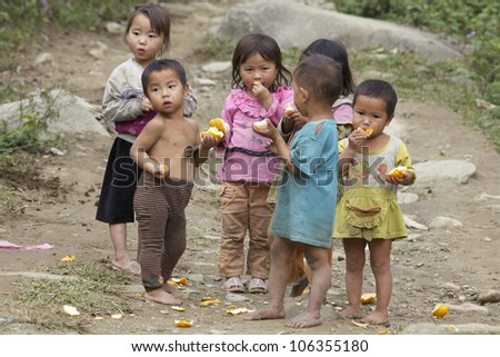 SAPA, VIETNAM- NOVEMBER 21: Six unidentified Vietnamese children play and eat in Sapa, Vietnam on November 21, 2010. Vietnam's 2011 population is 90,549,390 with 25% of the population age 14 and under