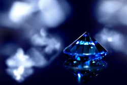 Sapphire or blue diamond with brilliant-cut and shiny background, closeup